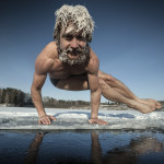 Man with frozen hair doing yoga exercise, parsva bakasana, on the ice